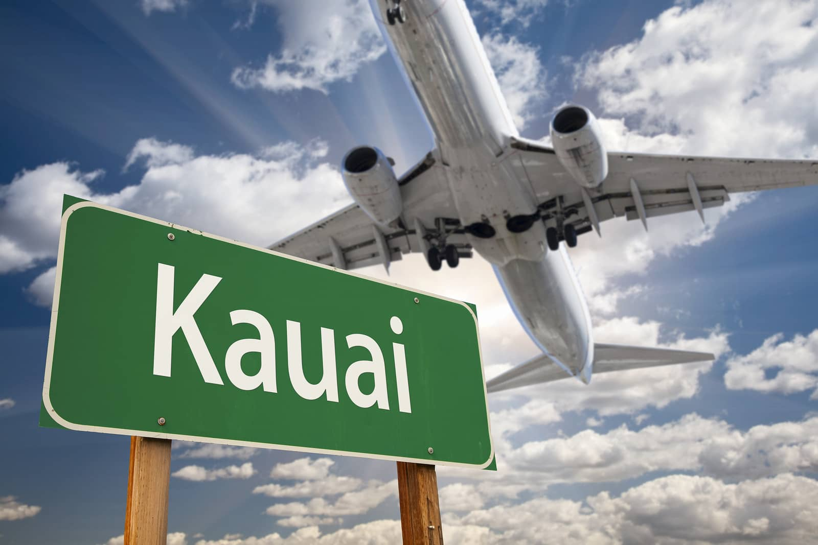 Kauai Green Road Sign and Airplane Above with Dramatic Blue Sky and Clouds
