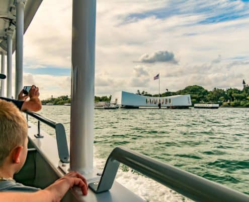 People on Boat with USS Arizona Memorial in background