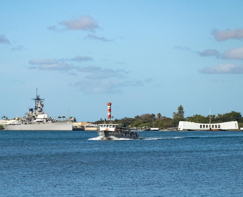 A Navy launch returns visitors from the Arizona Memorial with the USS Missouri in the background